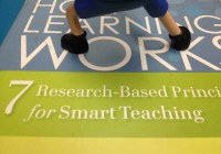 action figure feet standing on a book called How Learning Works